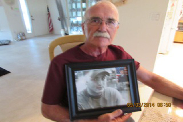 Walter Shersty poses with a photo of his son, Daniel, this week at his home in Port St. Lucie, Fla. (Photo courtesy Mary Ann Clate)