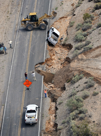 Road crews work to pull a truck that fell off the side of the road in Moapa on Tuesday, Sept. 9, 2014. Record flooding on Monday caused major highway damage.  (Photo by David Becker/Las Vegas Revi ...