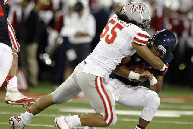 UNLV linebacker Tau Lotulelei (55) sacks Arizona quarterback Anu Solomon (12) during the first half of an NCAA college football game, Friday, Aug. 29, 2014, in Tucson, Ariz. (AP Photo/Rick Scuteri)