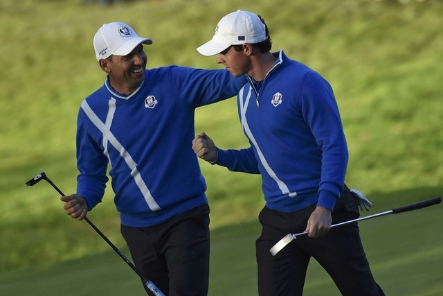 European Ryder Cup player Rory McIlroy, right, is congratulated by teammate Sergio Garcia after winning the hole on the 17th green during their foursomes 40th Ryder Cup match at Gleneagles in Scot ...