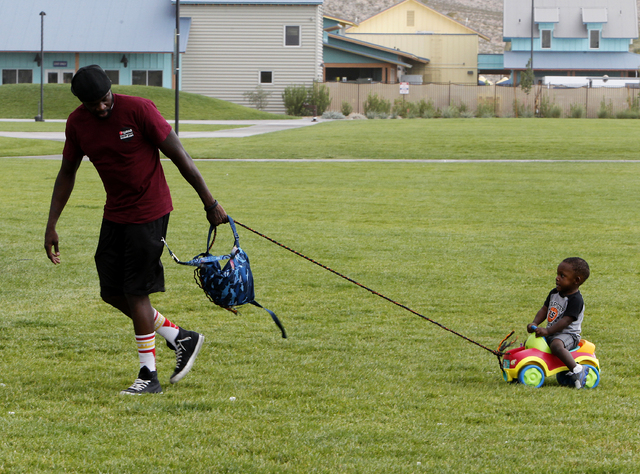 Lavelle Bonds, left, leads his son Messiah Bonds, 1, right, out of the rain and wind at Wilbur and Theresa Faiss Park in the southwest part of the Las Vegas valley on Sunday, Sept. 7, 2014. Rain a ...