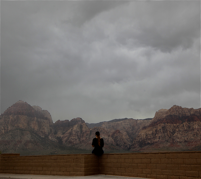 A woman looks at the clouds from an observation area in  Red Rock National Conservation Area on Sunday, Sept. 7, 2014. Rain and wind swept through the valley as the remnants of tropical storm Norb ...