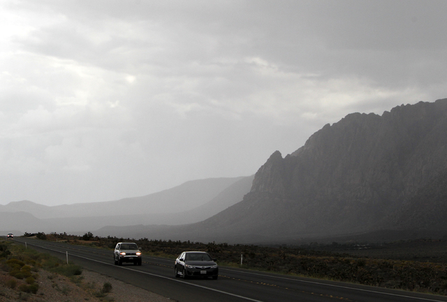 Cars travel along  on State Route 157 during a rain shower in Red Rock National Conservation Area on Sunday, Sept. 7, 2014. Rain and wind swept through the valley as the remnants of tropical storm ...