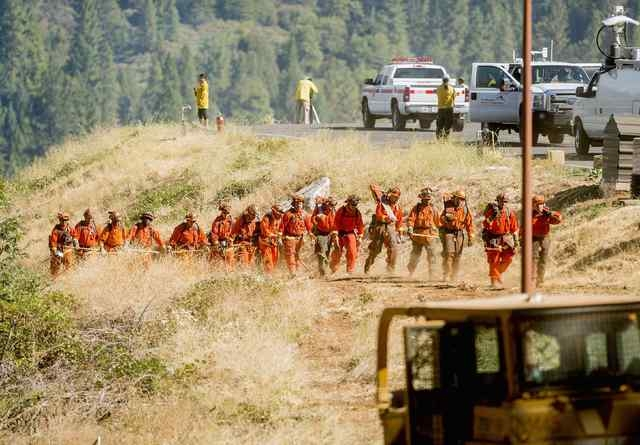 Inmate firefighters return to their truck after battling the King Fire near Fresh Pond, California, Wednesday, Sept. 17, 2014. The California wildfire racing through the El Dorado National Forest  ...
