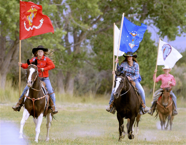 Patrice Stewart with Marine Corps flag, from left, Katelyn Rose with NV flag and Quint Bell with another service flag make a grand entry at the Ninety-Six Ranch NV 150 Celebration on August 9, 201 ...