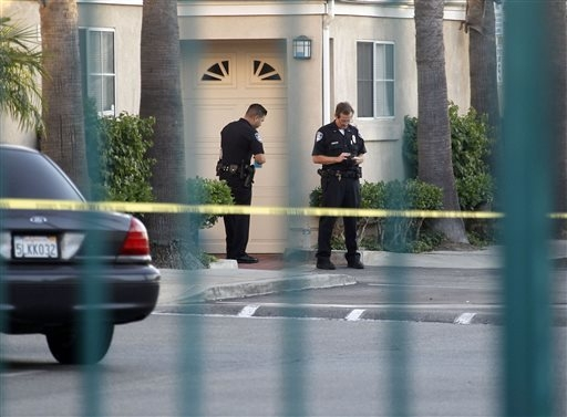 Police officers stand by the scene of a shooting in Bell Gardens, Calif., Tuesday, Sept. 30, 2014. (AP Photo/Nick Ut)