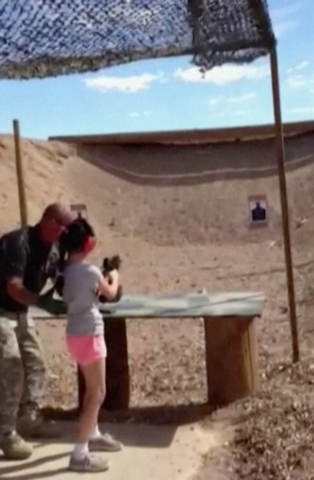 In this Aug. 25, 2014 image made from video provided by the Mohave County Sheriff Department, firing-range instructor Charles Vacca, left, shows a 9-year old girl how to use an Uzi. Vacca, 39, was ...