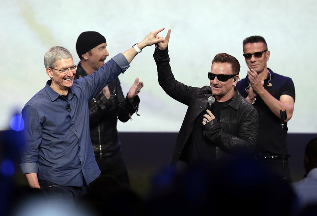 Apple CEO Tim Cook, left, greets Bono from the band U2 after they preformed at the end of the Apple event on Tuesday, Sept. 9, 2014, in Cupertino, Calif. (AP Photo/Marcio Jose Sanchez)
