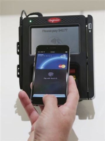 Apple Pay is demonstrated at Apple headquarters on Thursday, Oct. 16, 2014 in Cupertino, Calif. In announcing a Monday launch date, Apple CEO Tim Cook said deals have been made with hundreds of ad ...