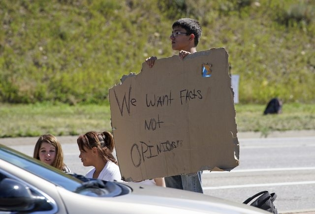 A protestor at Bear Creek High School holds up a sign while standing on a street near the school in Lakewood, Colorado September 25, 2014. (REUTERS/Rick Wilking)