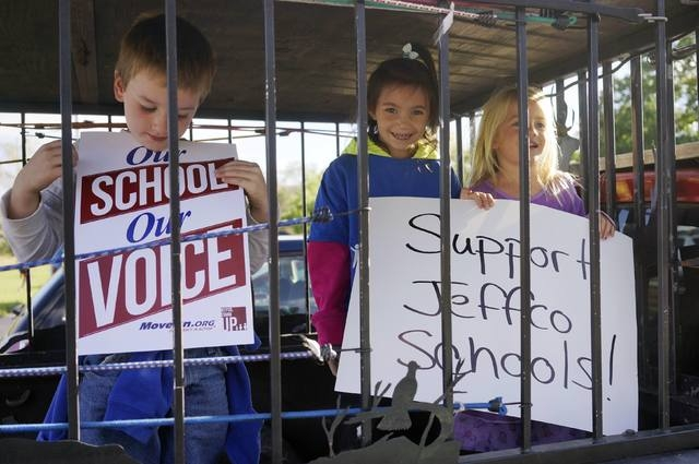 Children stand in a cage on the back of a pickup truck with signs, one provided by MoveOn.Org (L), in Golden, Colorado October 2, 2014, at a protest against proposed changes to the national histor ...