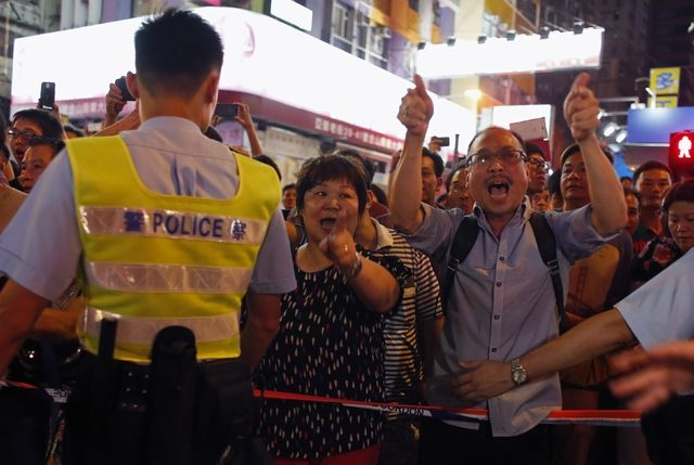 Anti-Occupy Central protesters yell at pro-democracy protesters behind a police cordon at Hong Kong's shopping Mong Kok district, where a main road is being occupied by pro-democracy protesters, F ...