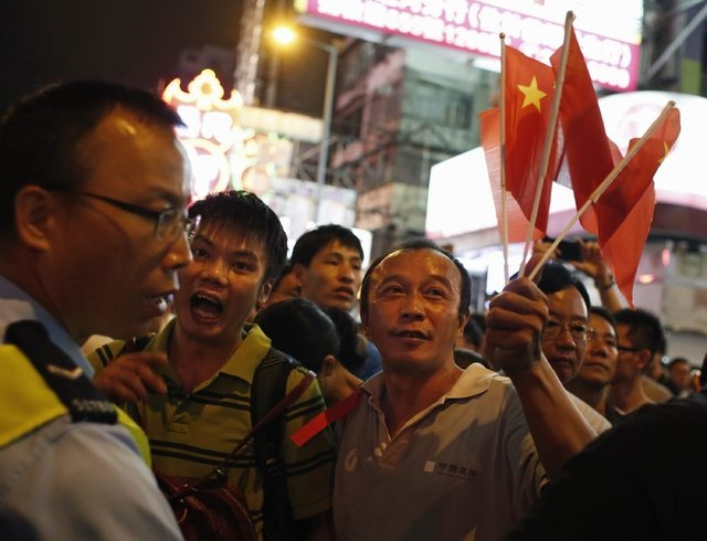 Anti-Occupy Central protesters hold Chinese national flags and urge the police to take action against pro-democracy protesters who are blocking a main road at Hong Kong's shopping Mong Kok distric ...
