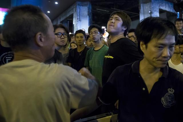 An anti-Occupy Central protester, left, argues with pro-democracy protesters on a main street at Hong Kong's Mong Kok district, Friday, Oct. 3, 2014. Violent scuffles broke out in one of Hong Kong ...