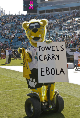 """Oct 5, 2014; Jacksonville, FL, USA; Jacksonville Jaguars mascot Jaxson carries a Pittsburgh Steelers """"Terrible Towel"""" and a sign after their game at EverBank Field. The Pittsburgh Steelers won 17- ..."""