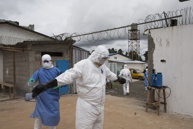 A health worker wearing protective equipment is disinfected outside the Island Clinic in Monrovia, September 30, 2014, where patients are treated for Ebola. After being refurbished by the Liberian ...