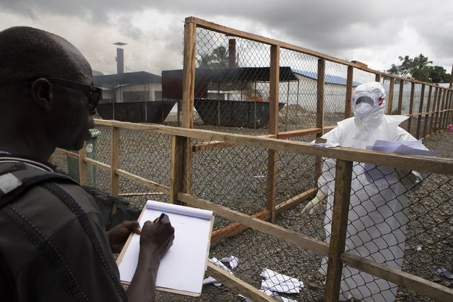 A health worker (R) wearing protective equipment provides his colleague with patient data at the end of his shift from the Ebola treatment centre at the Island Clinic in Monrovia, September 30, 20 ...