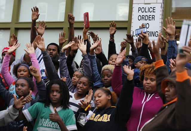 People hold up their hands in protest at a vigil in St. Louis, Missouri, Thursday, Oct. 9, 2014. (Reuters/Jim Young)