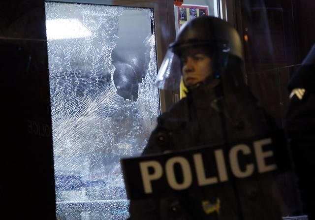 A police officer stands guard in front of a damaged storefront during a protest after a vigil in St. Louis, Missouri, Thursday, Oct. 9, 2014. (Reuters/Jim Young)