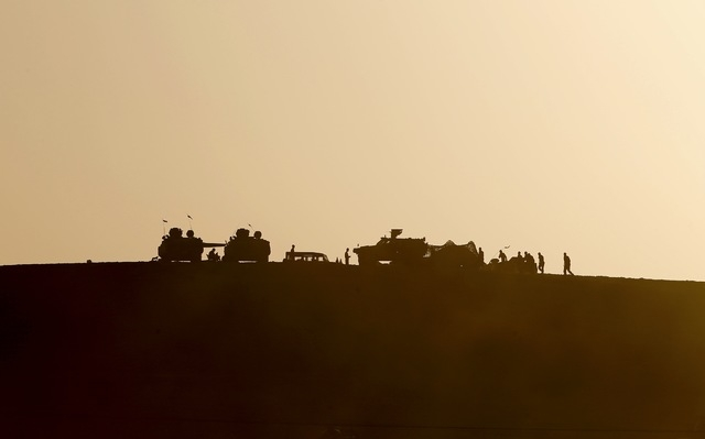 Turkish military are silhouetted on the top of a hill close to the border line between Turkey and Syria near Mursitpinar bordergate October 10, 2014. (REUTERS/Umit Bektas)