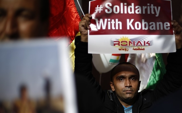 Kurdish men living in Bulgaria hold posters during a protest in solidarity with the Syrian Kurds in front of the European Parliament and European Commission offices in Sofia October 10, 2014. (REU ...