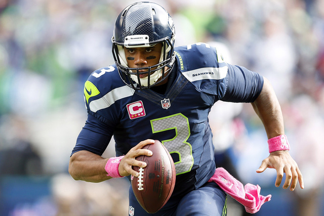 Seattle Seahawks quarterback Russell Wilson (3) rushes against the Dallas Cowboys on Oct. 12, 2014, during the second quarter at CenturyLink Field. (Joe Nicholson-USA TODAY Sports)