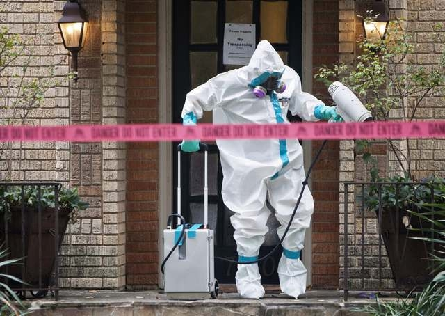 A member of the CG Environmental HazMat team disinfects the entrance to the residence of a health worker at the Texas Health Presbyterian Hospital who has contracted Ebola in Dallas, Sunday, Oct.  ...