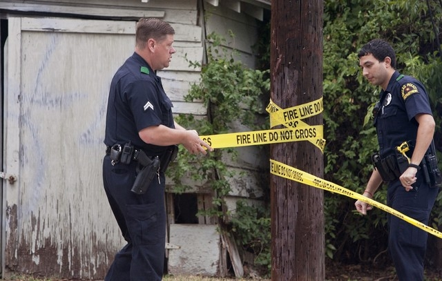 Dallas police officers put up tape to restrict entrance to the residence of a health worker at the Texas Health Presbyterian Hospital who has contracted Ebola in Dallas, Sunday, Oct. 12, 2014. The ...