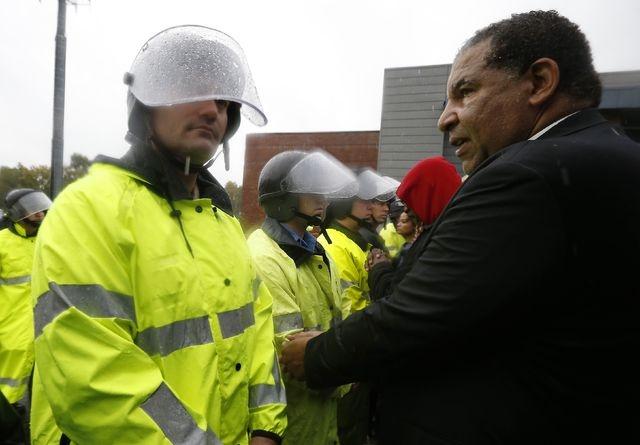 Religious leaders try to get detained in front of the riot police during a protest at the Ferguson Missouri, Police Department in Ferguson Sunday, Oct. 13, 2014. Hundreds of protesters converged i ...