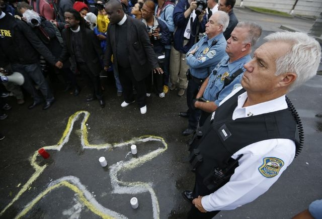 Police officers stand over a chalk outline of a body during a protest at the Ferguson, Missouri, Police Department, Monday, Oct. 13, 2014. (Reuters/Jim Young)