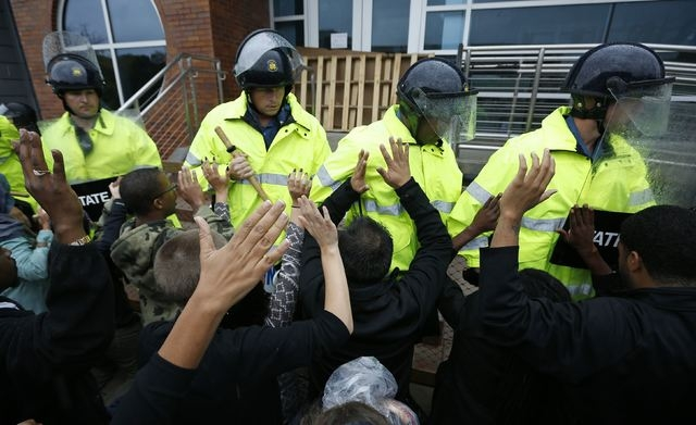 Protestors hold up their hands as the riot police move in during a protest at the Ferguson, Missouri, Police Department, Monday, Oct. 13, 2014. Hundreds of protesters converged in the pouring rain ...