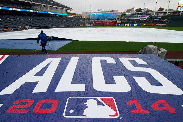 Oct 13, 2014; Kansas City, MO, USA; Rain collects on top of the dugout as grounds crew members work to keep the field dry before game three of the 2014 ALCS playoff baseball game between the Balti ...