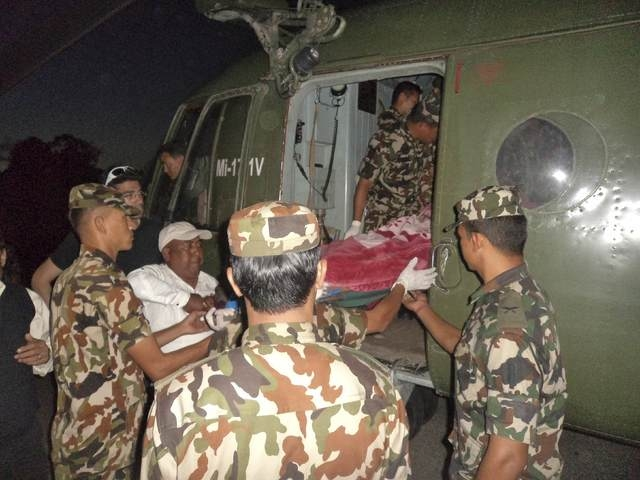 Nepalese army personnel carry a victim rescued from the avalanche inside a helicopter at Thorang-La in Annapurna Region in this, Wednesday, Oct. 15, 2014,  photo provided by Nepal's army. (Reuters ...