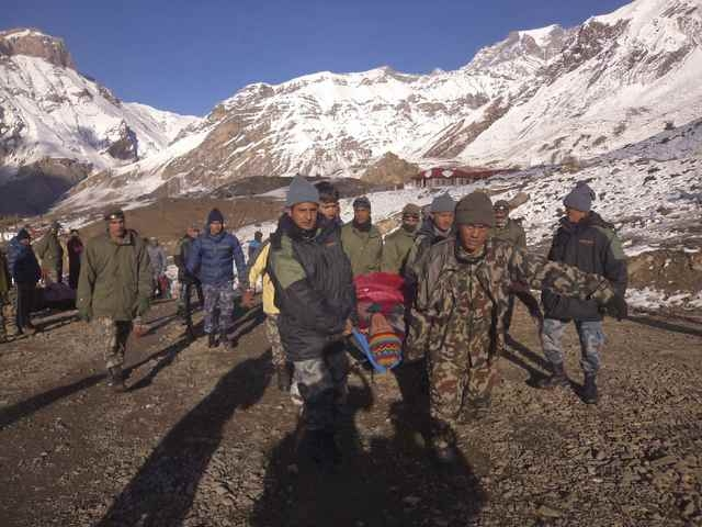 Nepalese army personnel carry a victim rescued from the avalanche at Thorang-La in Annapurna Region in this, Wednesday, Oct. 15, 2014, handout photo provided by Nepal's army. (Reuters/Nepal army h ...