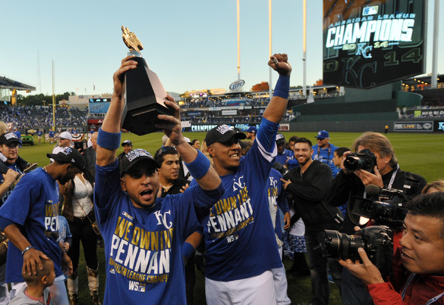 Royals second baseman Omar Infante (left) celebrates with catcher Salvador Perez (right) with the American League championship trophy after game four of the 2014 ALCS game against Baltimores at Ka ...