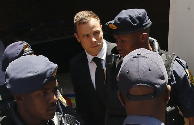 South African Olympic and Paralympic sprinter Oscar Pistorius, center, is escorted to a police van after his sentencing at the North Gauteng High Court in Pretoria, Tuesday, Oct. 21, 2014. Pistori ...