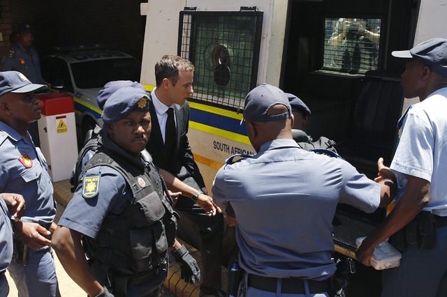 South African Olympic and Paralympic sprinter Oscar Pistorius, center, enters a police van after his sentencing at the North Gauteng High Court in Pretoria, Tuesday, Oct. 21, 2014. Pistorius was s ...
