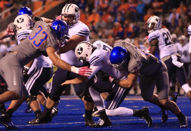 Boise State defensive lineman Kamalei Correa (8) and linebacker Gabe Perez (33) sack Brigham Young quarterback Christian Stewart (7) at Albertsons Stadium in Boise on Oct 24, 2014. The Broncos won ...