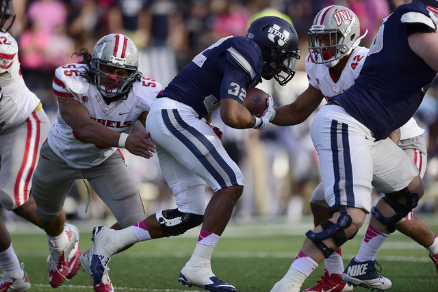 Utah State's Joe Hill (32) carries against Rebels linebacker Tau Lotulelei (55) and defensive back Peni Vea (42) on Oct. 25, 2014. The Aggies defeated the Rebels 34-20. (Ron Chenoy-USA TODAY Sports)