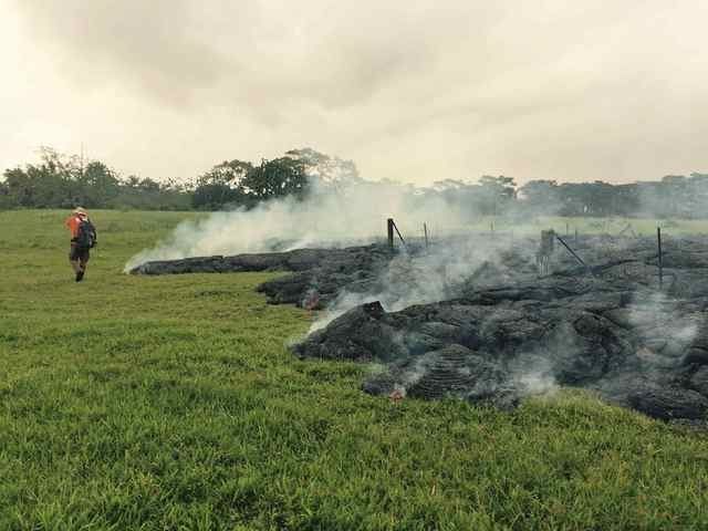 A Hawaii Volcano Observatory geologist maps the margin of the lava flow from the Kilauea Volcano in a U.S. Geological Survey image taken near the village of Pahoa, Hawaii, Sunday, Oct. 26, 2014. ( ...