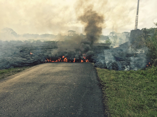 The lava flow from the Kilauea Volcano is seen crossing Apa'a Street/Cemetery Road near the village of Pahoa, Hawaii, Saturday, Oct. 25, 2014. (Reuters/U.S. Geological Survey handout)