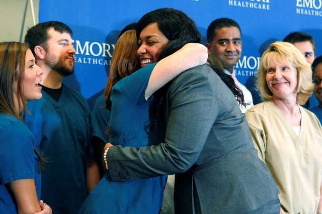 Amber Vinson hugs caregivers before her release from Emory University Hospital in Atlanta, Tuesday, Oct. 28, 2014. Vinson  was the second of two American nurses who became infected with Ebola whil ...