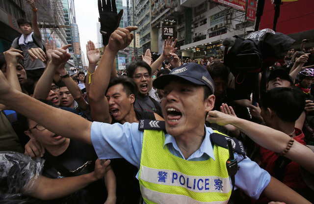 A police officer tries to hold back pro-democracy student protesters during a clash local residents in Mong Kok, Hong Kong, Saturday, Oct. 4, 2014. Friction between pro-democracy protesters and op ...