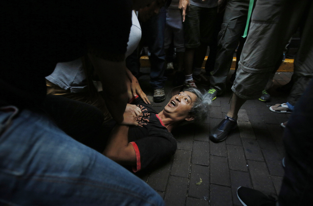 Pro-democracy student protesters pin a man to the ground after an assault during a scuffle with local residents in Mong Kok, Hong Kong, Saturday, Oct. 4, 2014. Friction between pro-democracy prote ...