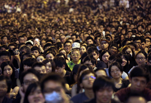 Thousands of pro-democracy activists attend a rally on the streets near the government headquarters, Saturday, Oct. 4, 2014 in Hong Kong. Hong Kong arrested 19 people, some believed to have organi ...