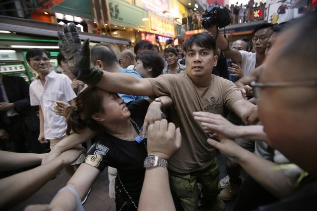 A woman is protected from the crowd by pro-democracy student protesters after a scuffle with local residents in Mong Kok, Hong Kong, Saturday, Oct. 4, 2014. Friction between pro-democracy proteste ...