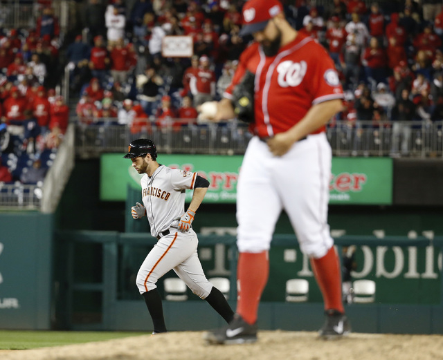 San Francisco Giants' Brandon Belt runs the bases past Washington Nationals pitcher Tanner Roark after hitting a solo home run in the 18th inning of Game 2 of baseball's NL Division Series in Nati ...