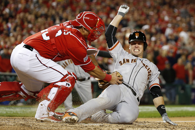 Washington Nationals catcher Wilson Ramos (40) tags out San Francisco Giants' Buster Posey during the ninth inning in Game 2 of baseball's NL Division Series in Nationals Park, Saturday, Oct. 4, 2 ...