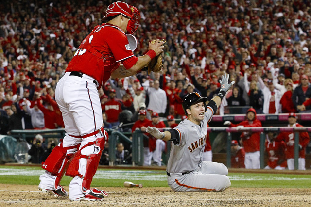 San Francisco Giants' Buster Posey signals to the umpire he's safe after sliding into home in the ninth inning of Game 2 of baseball's NL Division Series at Nationals Park, Saturday, Oct. 4, 2014, ...