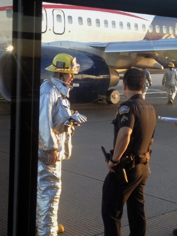 In this photo provided by Sara Seligman, authorities work the scene at Los Angeles International Airport after a Mexico City-bound Aeromexico jet hit its brakes after the left landing gear collaps ...
